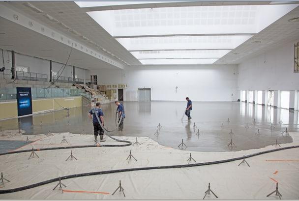 Mise en œuvre de la chape Technis de Bostik dans le futur centre de formation de Handball a Valentin. [©Julia Brechler / Bricolo Factory]