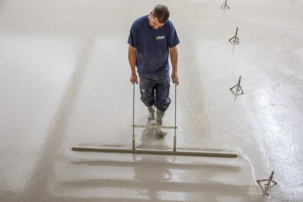 Un technicien assurait les opérations de finition de la chape fluide. [©Julia Brechler/Bricolo Factory]