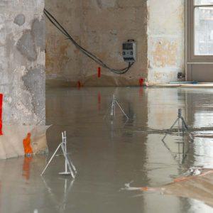 Coulage de la chape fluide anhydrite Excelio sur un chantier de rénovation de plancher. [©ACPresse]